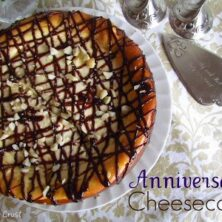 overhead ove cheesecake covered in chocolate and macadamia nuts on table cloth