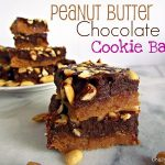 chocolate peanut butter cookie bars with peanuts on marble slab