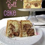 cinnamon roll cake slice on white plate with cake behind on platter