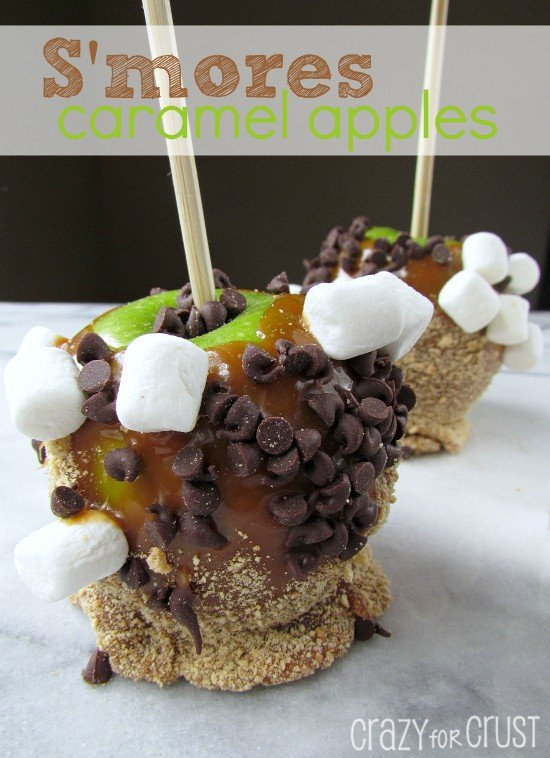 S'more Caramel Apples green apple on a stick with caramel, graham crackers, chocolate chips and marshmallows with words on photo