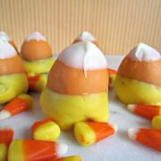 brownie bites dipped in chocolate to look like candy corn on marble slab with candy corn around