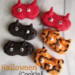 nutter butter cookies decorated to look like halloween masks: devils, cats, tigers