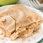 apple toffee bars on white plate with apple behind