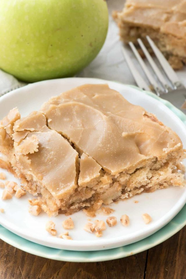 Apple Toffee Bars on a white plate with cracked caramel frosting and fork behind
