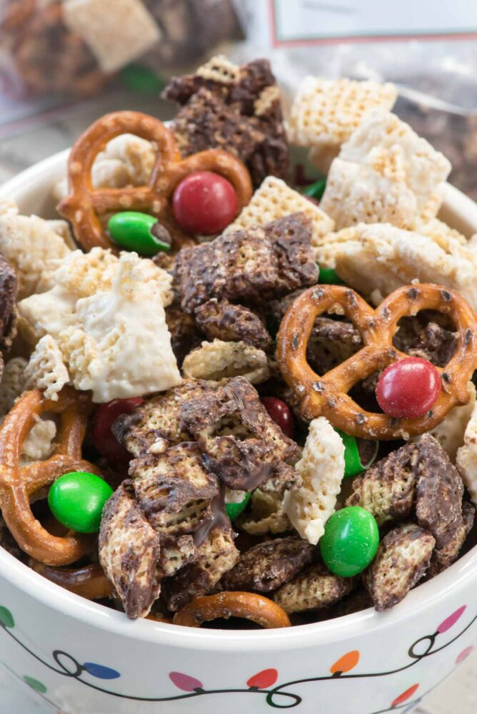 Elf Munch Chocolate coated Chex mixed with pretzels and candy in a holiday light bowl
