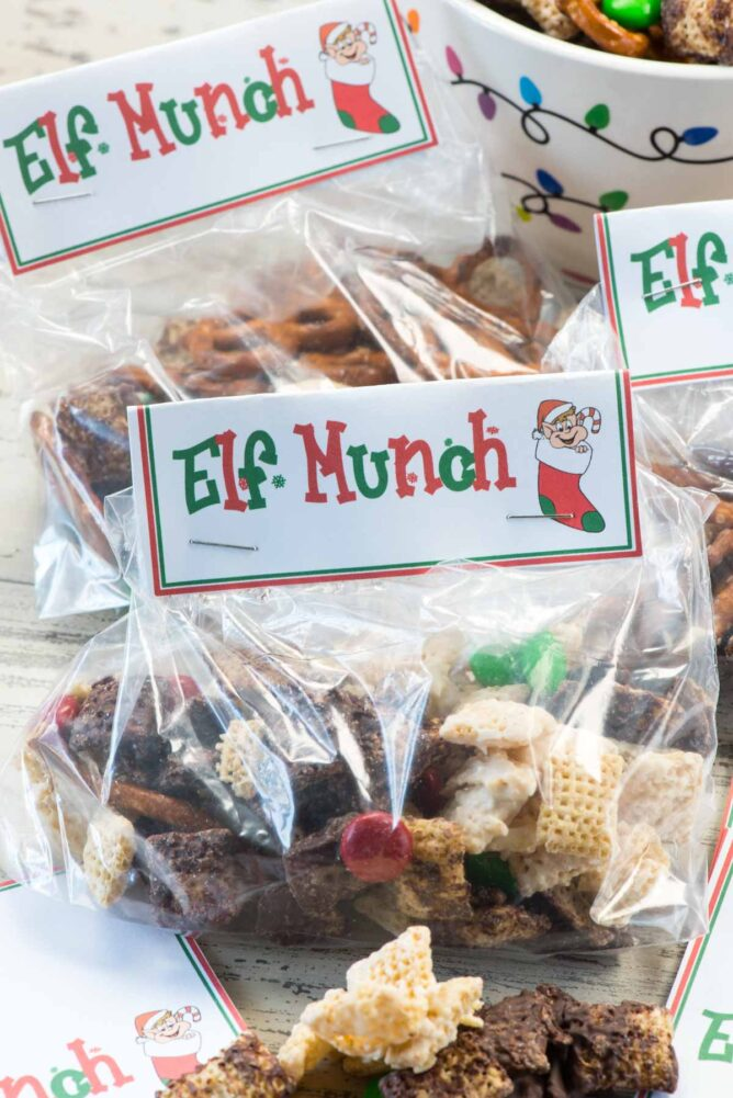 Elf Munch Chocolate coated Chex mixed with pretzels and candy baggies with tags that say elf munch