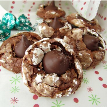 chocolate blossom cookies with hersheys kiss on top in a pile on christmas parchment paper