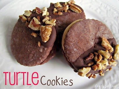turtle cookies chocolate sandwich cookies with caramel inside and pecans on top on white plate with words