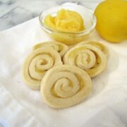 spiral sugar cookies with lemon curd on white napkin with lemon curd behind and lemon