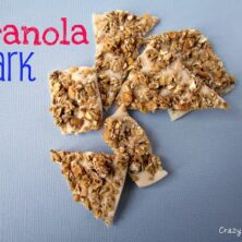 granola bark white chocolate with granola on top on blue paper with words