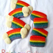 sugar cookies dyed rainbow colors with white clouds at ends on white linen