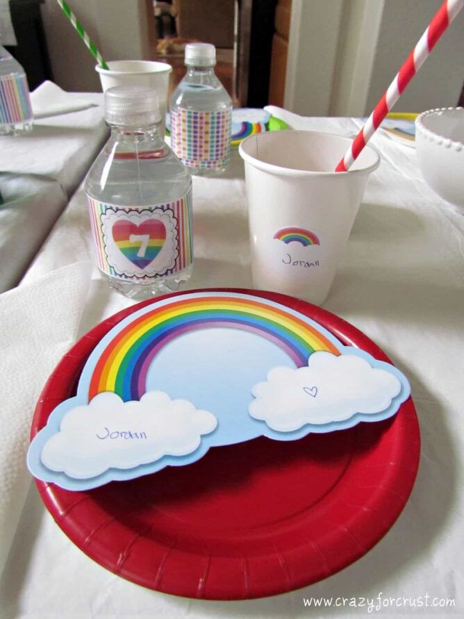 rainbow birthday party place setting with red plate, decorated water bottle and place card