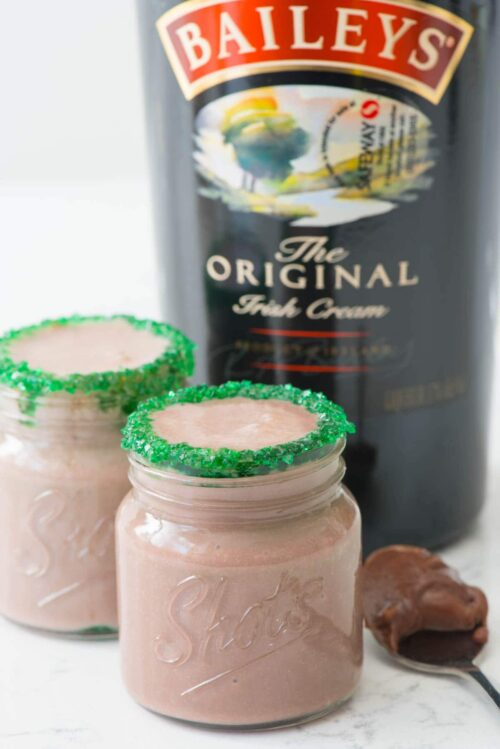 2 Baileys' pudding shots in small jars with a bottle fo Baileys'