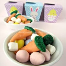 cadbury eggs marshmallows and bugles dipped in chocolate to look like carrots in white dish