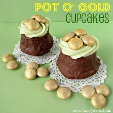 two cupcakes dipped in chocolate with green frosting and gold colored candy to look like pot o gold cupcakes
