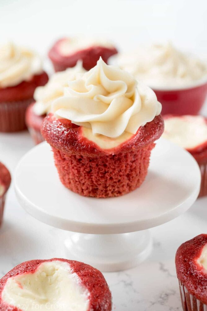 Red Velvet Cheesecake cupcake on a white cake stand