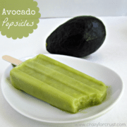Avocado popsicle missing one bite on a white plate, with an avocado in the background, graphic title on the top right.