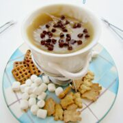 Cup full of cookie dough fondue on a plaid plate with marshmallows, pretzels and teddy grahams on plate