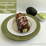 Chocolate twist doughnuts with avocado cream filling on a white plate, on top of a green charger, with a bowl of avocado cream, plus an avocado in the background.