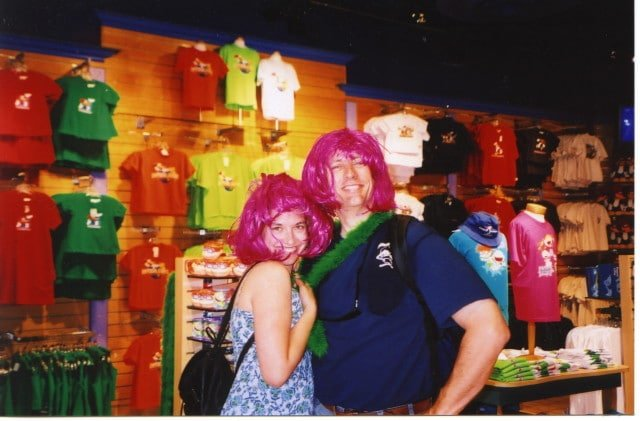 couple wearing pink wigs in store