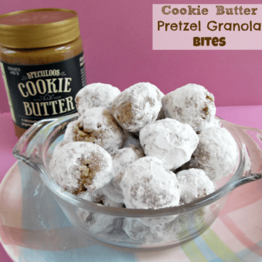 cookie butter pretzel granola bites in a clear bowl on top of a pastel plate with the cookie butter jar in the background and the graphic title in the top right hand corner