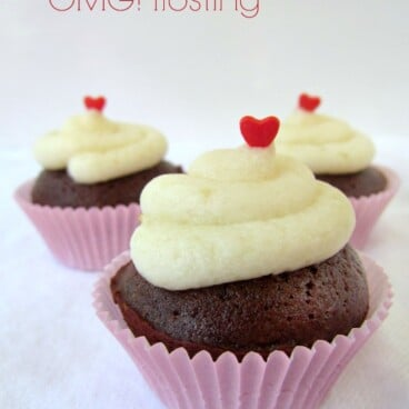 Brownie Bites with white frosting on top and a heart sprinkle on white background