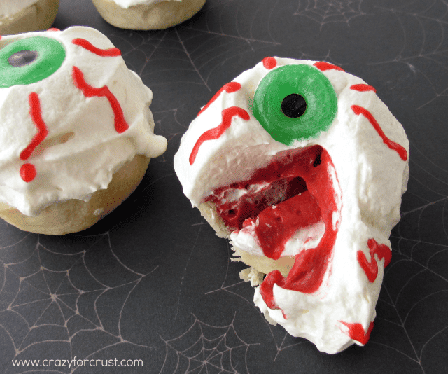 Red Velvet Eyeball Pies with whipped cream and red frosting eyes with lifesaver pupils cut open to see inside