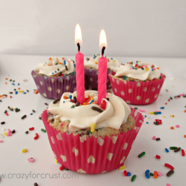 funfetti cupcakes with rainbow sprinkles, front cake has two birthday pink candles