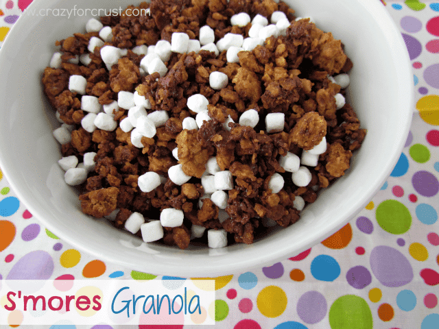 smores granola with mini marshmallows in white bowl on colorful linen and words on photo