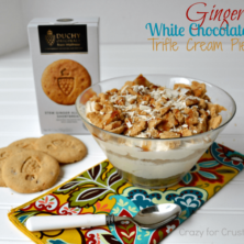ginger white chocolate trifle in a trifle dish with printed napkin underneath and spoon, and ginger cookies
