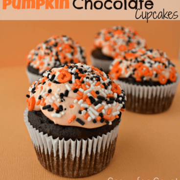 chocolate cupcakes made with pumpkin with orange frosting and halloween sprinkles on orange background