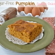 Sugar free pumpkin cake on a doily with a white fork, green plate, brown eggs and spilled cinnamon.