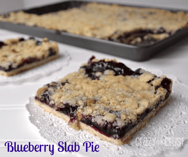 Blueberry Slab Pie square piece on a white doily with whole pie in the background on a metal sheet pan