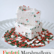 Two Funfetti marshmallows on top of Christmas colored sprinkles on a white plate, graphic image on the bottom.