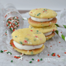 Funfetti sandwich cookies on a white napkin with holiday sprinkles poured around them.