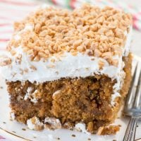A Gingerbread Poke Cake is the perfect Christmas cake recipe! Gingerbread cake is filled with butterscotch and gingersnaps and topped with whipped cream and toffee bits!