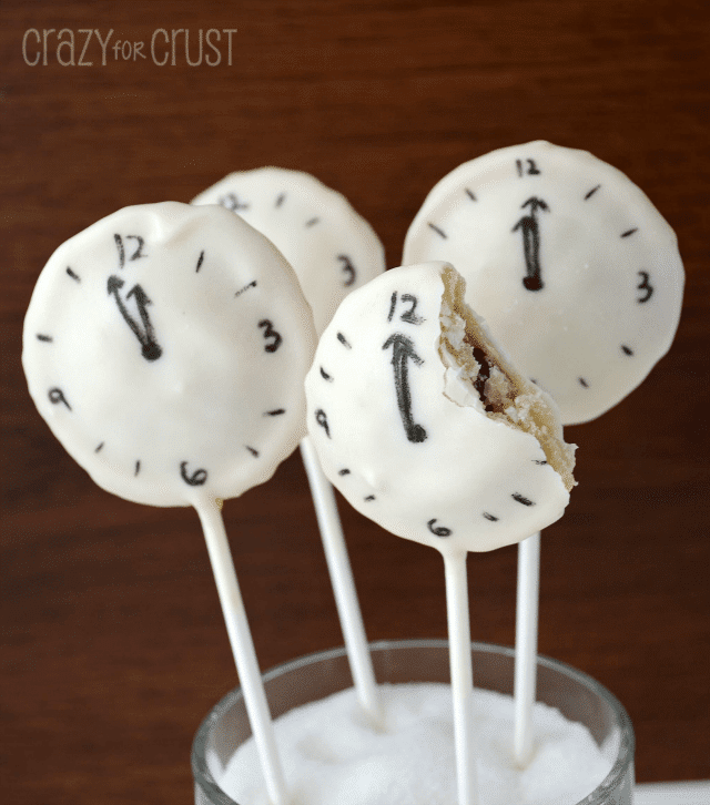 Clock pie pops, with one pop having a bite taken out of.