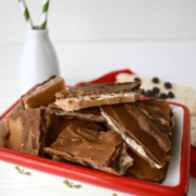 Peanut butter chocolate toffee bark in a red and white bowl, with glass jar holding straws in the background.