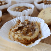 Pecan praline cheesecakes in white cupcake liners on a wooden board.