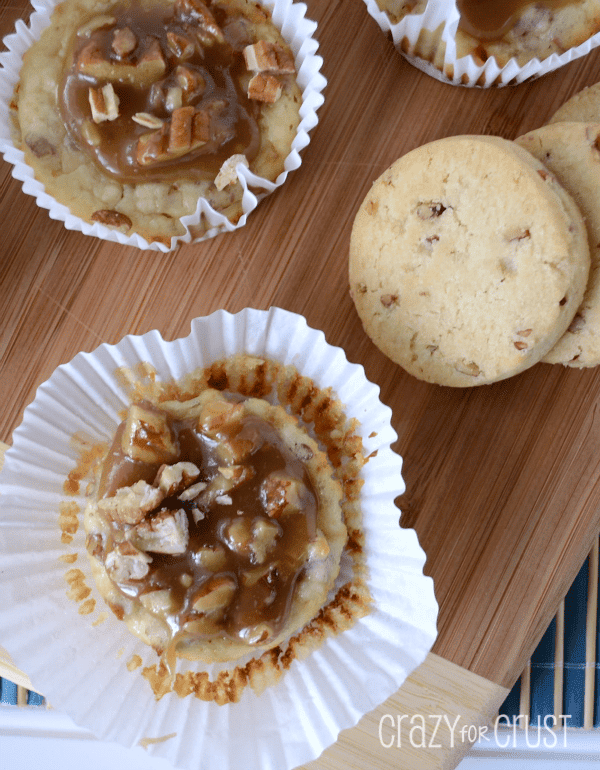 pecan praline cheesecakes in white liners on cutting board with nuts on top