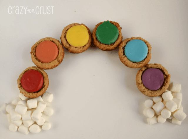 peanut butter cookies cups with rainbow colored candies in the center in the shape of a rainbow with marshmallow clouds