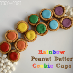 Rainbow peanut butter cookie cups in the shape of a rainbow with mini marshmallows at the end, graphic title on the bottom right.