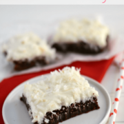 fudgy brownies with coconut frosting on white plate with straw and red napkin