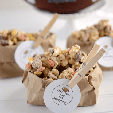 Peanut butter kitchen sink popcorn in a brown paper bag with a clothespin holding a football graphic, graphic title on the bottom.