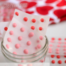 pink and red candy buttons on white background and in jar