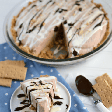 Skinny Frozen S'mores Pie with slice on white plate and pie with slice missing