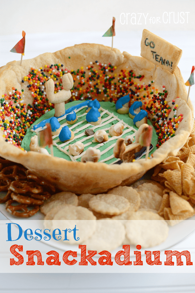 Snackadium made out of crescent rolls with icing field and sprinkle people on white plate with pie crust and cracker dippers