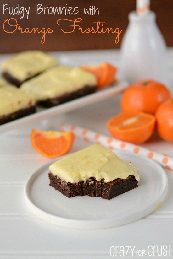 orange frosted brownies on white plate with oranges in background