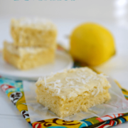 lemon coconut blondies on parchment paper and colorful napkin topped with coconut