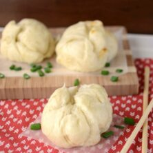 pork buns on parchment and patterned napkin with chopsticks